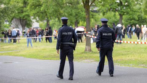 Polizisten kontrollieren Menschenmengen in einem Park