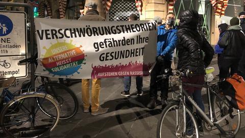 """Ein Demonstrant hält ein Banner mit der Aufschrift """"Verschwörungstheorien gefährden Ihre Gesundheit."""""""