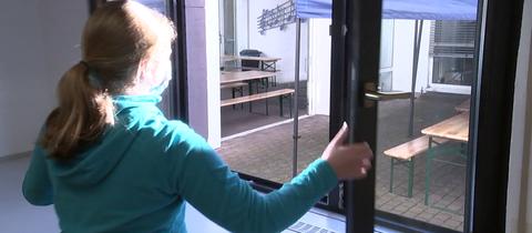 Alina öffnet ein Fenster des Klassenzimmers der 6b