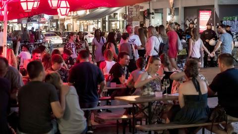 Nachtleben auf der Straße - viele Menschen sitzen und stehen dicht beieinander.