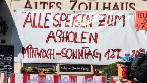 """""""Alle Speisen auch zum Abholen"""" steht auf einem Transparent vor einem Frankfurter Restaurant."""