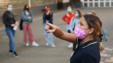 Lehrerin weist Schüler in Corona-Regeln ein auf Pausenhof