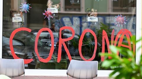 """Das Schaufenster eines Friseurgeschäfts """" auf der Berger Straße in Frankfurt ist mit dem Wort """"Corona"""" bemalt."""