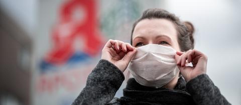 Frau mit Atemschutzmaske vor einer Apotheke