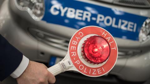"""Kelle und Polizeiauto mit Aufschrift """"Cyber-Polizei"""""""