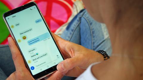 """Ein Mädchen hält ein Smartphone in der Hand, auf dem ein Chat mit meherern Nachrichten und der Frage """"Bock auf Live-Chat?"""" zu sehen ist"""