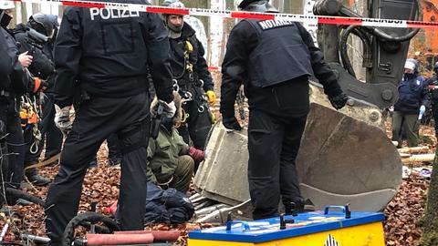Ein Aktivist hat seine Hand in einem Betonklotz, umringt von Polizisten