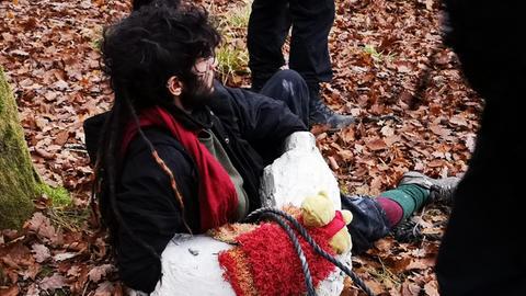 Ein Demonstrant hat seine Arme einbetoniert.