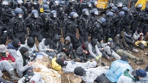 Mit einer Polizeikette versuchen die Beamten Aktivisten zurückzudrängen, die in eine Rodungsfläche eingedrungen waren.