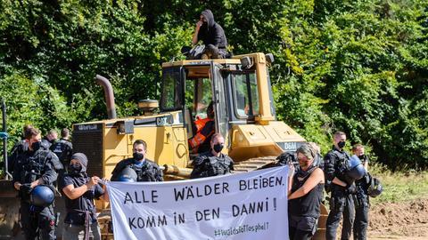 """Vermummte Aktivisten und Polizisten stehen um eine Planierraupe herum. Auf einem Transparent steht """"Alle Wälder bleiben""""."""