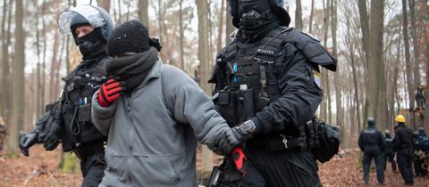 Zwei Polizisten führen eine Aktivistin ab.