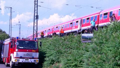 Personen steigen aus einem wartenden Zug vor dem Darmstädter Hauptbahnhof aus.