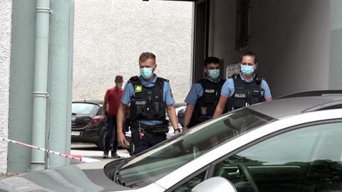 Polizeikräfte betreten einen Hinterhof in Darmstadt.