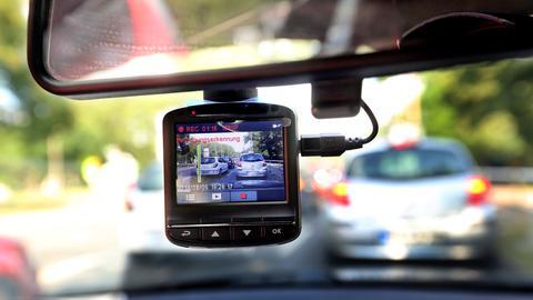 Eine sogenannte Dashcam, befestigt an der Windschutzschreibe, filmt den Straßenverkehr aus einem Auto.