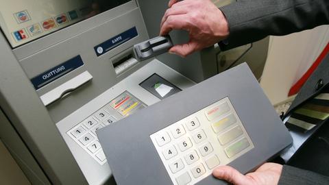 Ein Sparkassen-Mitarbeiter demonstriert an einem Geldautomaten die «Skimming»- Technik.