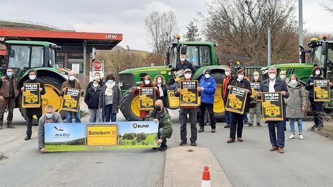 """Demonstrierende Menschen mit Plakaten von """"Nabu"""" und """"BUND"""" in der Hand posieren für den Fotografen."""