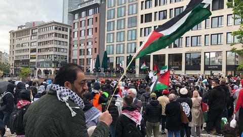 Ein Mann schwenkt eine palästinensische Flagge, hinter ihm haben sich die Demonstrierenden versammelt.