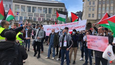 Menschen schwenken palästinensische Flaggen.