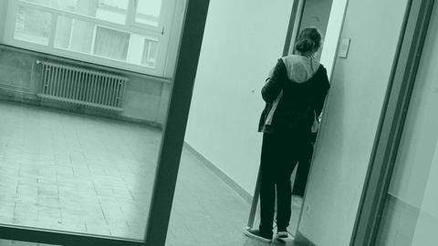 Ein Mädchen schaut durch eine geöffnete Tür in einen Raum.