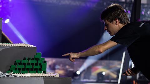Ein Teammitglied zählt nach dem Rekordversuch die Dominosteine die noch stehengeblieben sind