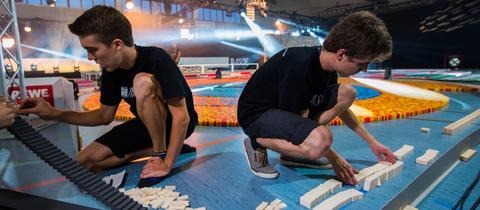 Teammitglieder bauen kurz vor dem Start mehrere Reihen von Dominosteinen neu auf.