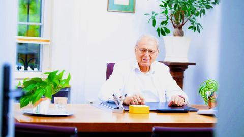 Dr. Freiherr von Rosen sitzt am Schreibtisch