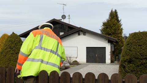 Ein Polizist betritt am 26.02.2017 das Grundstück eines Hauses in Höfen bei Königsdorf im Landkreis Bad Tölz-Wolfratshausen (Bayern), in dem zwei Menschen getötet und eine weitere Person schwer verletzt wurden.