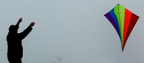 Ein Mann lässt bei Nebel auf dem Feldberg im Taunus einen Drachen steigen.