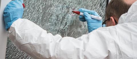 Ein Polizist untersucht ein Einschussloch an der Unterkunft in Dreieich
