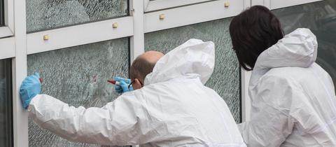 zwei Menschen in weißen Anzügen knien vor einer zersplitterten Glasscheibe.