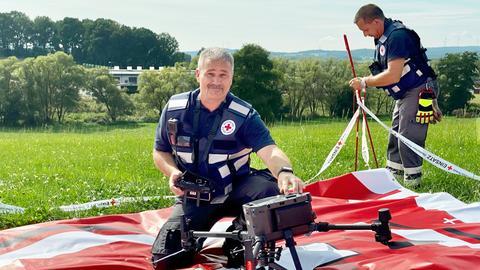 Ein Rettungssanitäter vom Deutschen Roten Kreuz hantiert an der neuen Drohne für Notfalleinsätze und hockt dabei auf dem Boden.