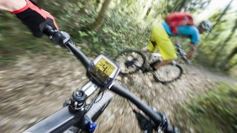 Foto von drei Mountain-Bikern, die auf ihren E-Mountain-Bikes durch einen Wald cruisen.