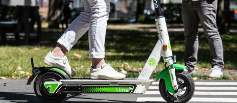 Frau überquert auf dem E-Scooter einen Zebrastreifen