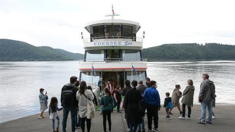 """Viele Touristen stehen vor einem Auflugsschiff und wollen an Bord gehen. Das Schiff trägt die Aufschrift """"Edersee"""". Im Hintergrund ist der weite See und die umgebende Landschaft zu sehen."""
