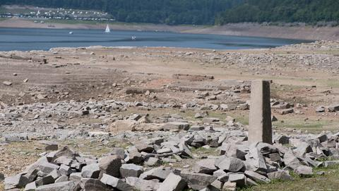 Ein Grenzstein und viele steinerne Überreste - im Hintergrund der Edersee mit Niedrigstand.