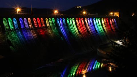 Beleuchtete Edertalsperre mit Wasserlauf.