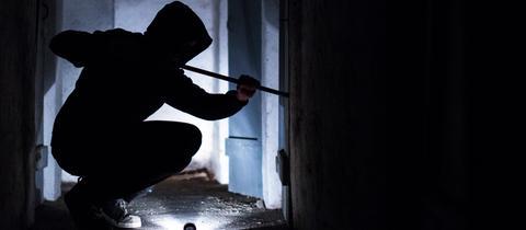 Einbrecher, der nachts in Fenster einsteigt