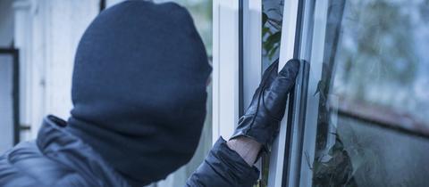 Einbrecher öffnet Fenster