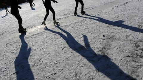 Die Beine von drei Menschen, die Schlittschuhlaufen.