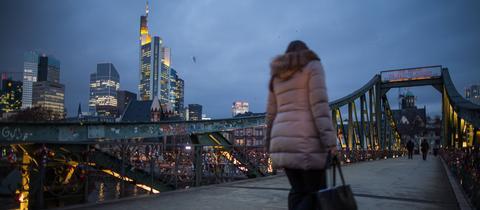 Eine Frau geht über den Eisernen Steg in Frankfurt
