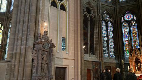 Besucher stehen vor einem Schrein. Während der Großteil der Kirche düster ist, gibt es neben den Menschen bereits einen hellen, pinken Farbstreifen