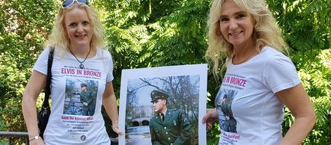 Meike Berger (li.) und Angela Storm halten auf der Usa-Brücke in Bad Nauheim ein Foto von ihrem Idol Elvis Presley hoch.
