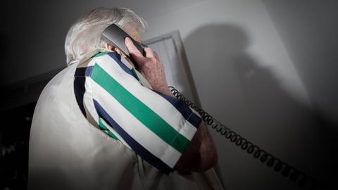 Ein alter Mensch mit Telefon in der Hand.