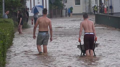 Menschen auf einer überschwemmten Straße in Etzen-Gesäß im Odenwald