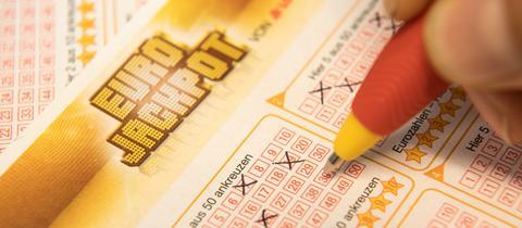 Mit einem Stift werden Zahlen in Eurojackpot-Schein angekreuzt