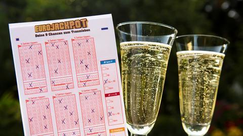 Eurojackpot-Schein und zwei Sektgläser - Symbolbild
