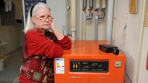 Evelyn Hinzpeter im Keller ihres Hauses - sie stützt sich mit den Ellenbogen auf ihre Heizungsanlage.