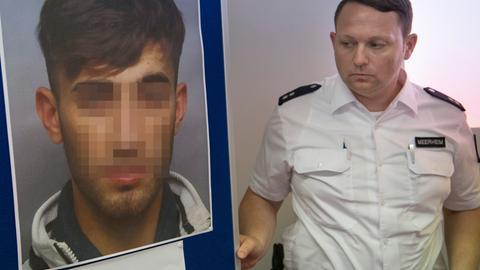 Ein Polizist mit einem Foto des gesuchten Ali B.