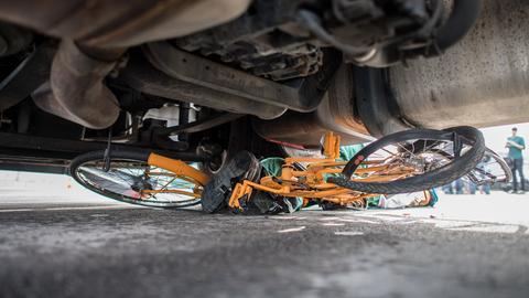 Ein Dummy und sein Fahrrad liegen bei einem Crash-Test unter einem Lastwagen.