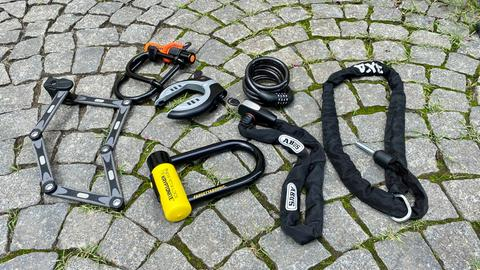 eine Auswahl an Fahrradschlössern liegt auf dem Boden